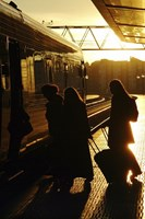 Silhouetted people boarding a train